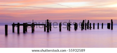 Panoramic image, ratio 12:5. Sunrise over the old pier in Swanage, Dorset (England)