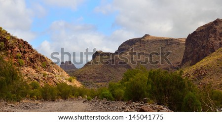 Panoramic image with rocky mountains in the interior of Tirajana ravine, Gran canaria, Canary islands - stock photo