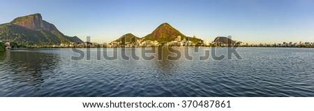 Panoramic image with the Christ Redeemer and Rodrigo de Freitas lagoon with vegetation and constructions around - stock photo