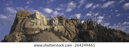 Panoramic image with white puffy clouds behind Presidents George Washington, Thomas Jefferson, Teddy Roosevelt and Abraham Lincoln at Mount Rushmore National Memorial, South Dakota - stock photo