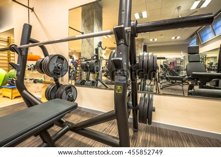 Panoramic interior view of modern equipment in the gym with mirrors on the walls, machines for sport, fitness and wellness.