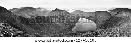 Panoramic landscape from the summit of Helvellyn, England's 2nd highest mountain, including Red Tarn and Striding Edge, in black and white - stock photo