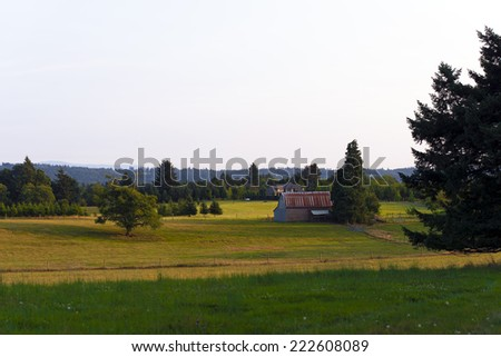 Panoramic landscape of fields and meadows with trees and yellowed grass and green, as well as a farmhouse and wooden plank barn under the red roof. Magnificent landscape in the famous Columbia Gorge. - stock photo