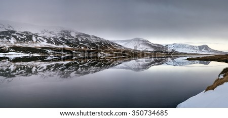 Panoramic landscape of snowy mountains reflecting in the still lake water with mist creeping in, serene idyllic vista - stock photo