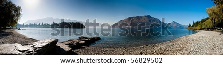 Panoramic landscape view of mountain lake and clear blue sky. - stock photo