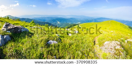 panoramic landscape with narrow meadow path in grass among white stones on top of mountain range in morning light - stock photo