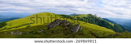 Panoramic mountain landscape with cloudy stormy sky and green sunny foreground grass - stock photo