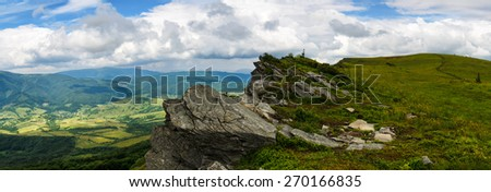 Panoramic mountains landscape with grassy hills and slopes and large rock and cloudy sky - stock photo