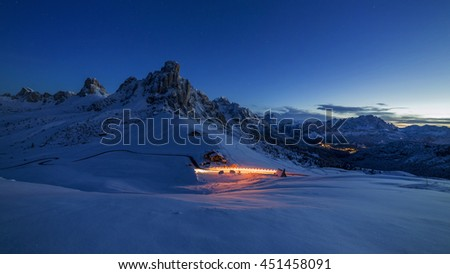 Panoramic night view on Passo Ghiau and Cima ra Gusela with lights of car, Dolomites - Italy