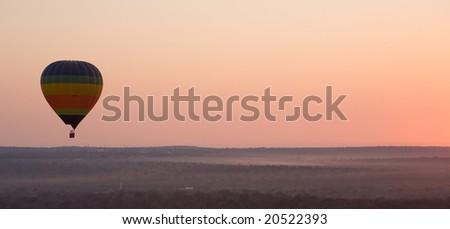 Panoramic of a hot air balloon at sunrise - stock photo