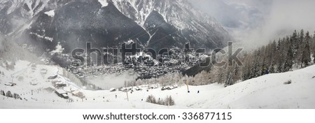 Panoramic of Courmayeur mountain resort, ski slopes and cable cars during snowfall. Italian Alps, Valle d'Aosta, Italy. - stock photo