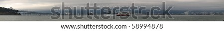 Panoramic of Ferry racing by the Bay bridge and the east bay on a foggy smoggy day.  Featuring the port of oakland and several boats in the background. - stock photo
