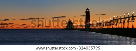 Panoramic of sunset at the Grand Haven South Pierhead Inner Light with Entrance Light in background in Grand Haven State Park in Grand Haven, Michigan - stock photo