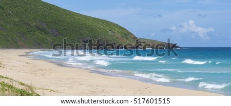 Panoramic of waves from turquoise blue Caribbean Sea rolling onto remote Resaca Beach on Isla Culebra in Puerto Rico under sunny sky