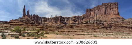Panoramic photo along the Canyonlands National Park White Rim Trail near  Moab Utah.  Showing Washer Woman Tower and Arch, Monster Tower and  Sandcastle formations along with other rock formations.  - stock photo