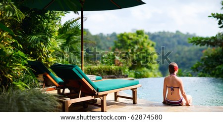 Panoramic photo of beautiful woman relaxing at swimming pool - stock photo