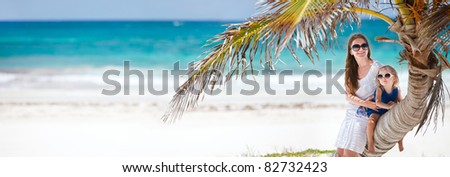 Panoramic photo of mother and daughter sitting on palm at Caribbean beach - stock photo