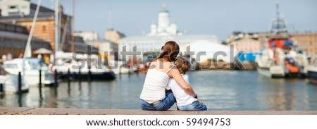 Panoramic photo of mother and son sitting on jetty and enjoying beautiful views central Helsinki Finland - stock photo