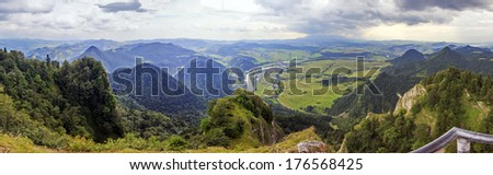 Panoramic photo of Pieniny Mountains, Poland with large vistas of space down below:  peaks, forest, meadows, fields and villages. - stock photo