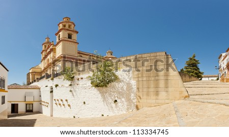 Panoramic photo of the pueblos blancos Olvera. Overviewing plaza with neoclassical cathedral. Iglesia de Nuestra Senora. Old white village. Blue sky. Cadiz. Andalusia. Spain.