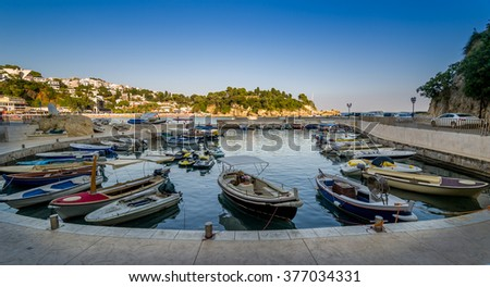 Panoramic photo of traditional fishing boats pier at calm summer evening. Ulcinj, Montenegro.