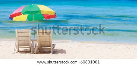 Panoramic photo of tropical beach with two chairs and colorful umbrella - stock photo