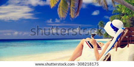 panoramic photo of woman drinking wine and looking at touch pad on tropical beach - stock photo
