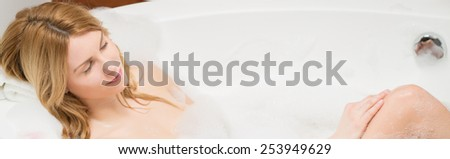 Panoramic photo of young beautiful woman lying in a bathtub - stock photo