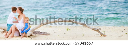 Panoramic photo of young beautiful woman with two kids sitting on tropical beach - stock photo
