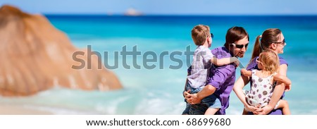 Panoramic photo of young family with two kids on tropical vacation