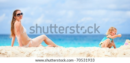Panoramic photo of young mother and her daughter at beach