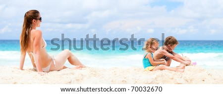 Panoramic photo of young mother and her two kids at beach - stock photo