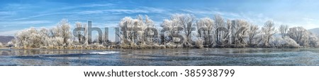Panoramic photo winter river with frost covered trees