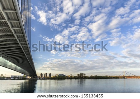 Panoramic photograph of Belgrade and Sava river with the Bridge Over Ada and the New Railroad bridge in the distance, made at dusk, from the lower tip of Ada Ciganlija river isle.  - stock photo
