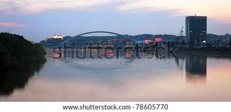 panoramic picture of Bratislava cityscape at dusk with reflection in the Danube river, illuminated Bratislava castle in background, Slovakia - stock photo