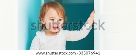 Panoramic portrait of a happy toddler girl inside  - stock photo