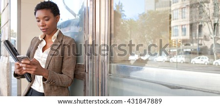 Panoramic portrait of african american business woman leaning on a reflective glass office building outdoors, using a smart phone, city exterior. Professional black woman using technology, exterior.