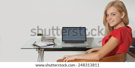 Panoramic portrait of an attractive student using laptop technology at home to study and do her homework, sitting at her desk with a computer and paperwork. Young professional smiling indoors. - stock photo