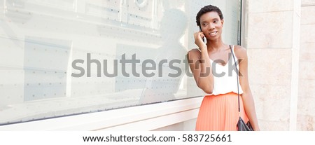 Panoramic portrait of beautiful african american professional woman in phone call conversation, smiling with shopping bags, office building in city outdoors. Black female using technology, lifestyle.