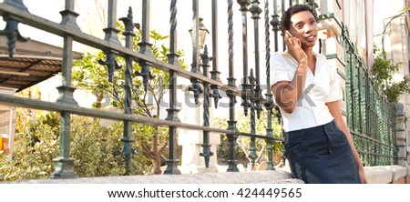 Panoramic portrait of elegant african american business woman in classic city with iron fence, using a smart phone on phone call, smiling in sunny outdoors. Ethnic professional woman, exterior. - stock photo