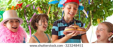 Panoramic portrait of group of children in fancy dresses at a colorful birthday party in bright home garden. Cake with candle, joyful expressions outdoors lifestyle. Kids activities and fun. - stock photo