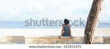 Panoramic rear view of a stylish african american black young woman sitting by white sand beach contemplating the sea on a sunny summer holiday destination, outdoors. Travel lifestyle, exterior. - stock photo