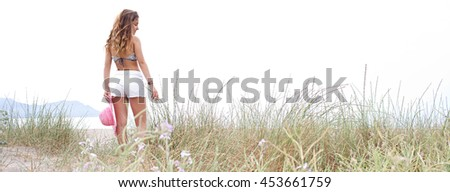 Panoramic rear view of young teenager girl on sand dunes relaxing, feeling touching long grass with hand, by the sea on summer holiday, outdoors nature. Travel and healthy lifestyle, beach exterior. - stock photo