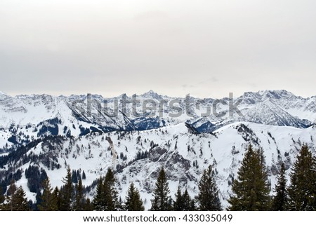 Panoramic scene of snow-covered alpine mountain peaks looking across the top of a pine forest to rugged mountains and valleys - stock photo