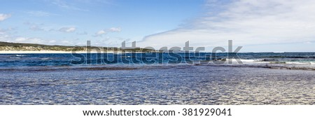 Panoramic  scenic view of the tide ebbing out from the   famous white sandy  surfing beach  at Margaret River south western Australia  on a calm cloudy afternoon in  early summer . - stock photo