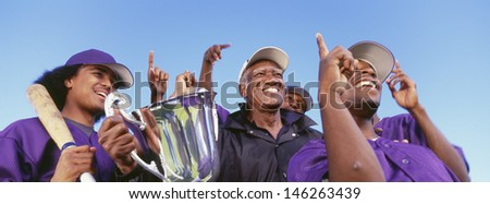 Panoramic shot of cheerful baseball players with trophy celebrating victory against clear sky - stock photo