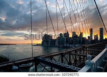 Panoramic shot of Manhattan skyline and Liberty island from the Brooklyn bridge at dusk. - stock photo