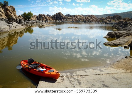 Panoramic shot of picturesque, tranquil Watson Lake, Prescot, with a bright orange canoe in the foreground on a sunny morning with sparse clouds in the bright blue sky reflecting in the calm waters  - stock photo