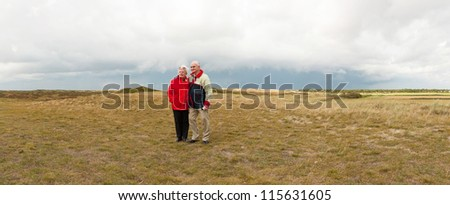 Panoramic shot of senior retired couple enjoying the outdoors. Dutch dune landscape with stormy cloudy sky. Lonely man. The Netherlands. Wadden island. Texel. - stock photo