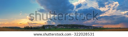Panoramic shot of the sunset in the countryside. Dramatic sky with clouds, field and rural houses on a background of trees. - stock photo